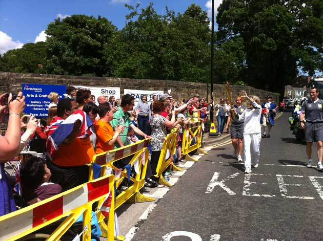 Art makers from Henshaws Arts & Craft Centre wave the torch on its way