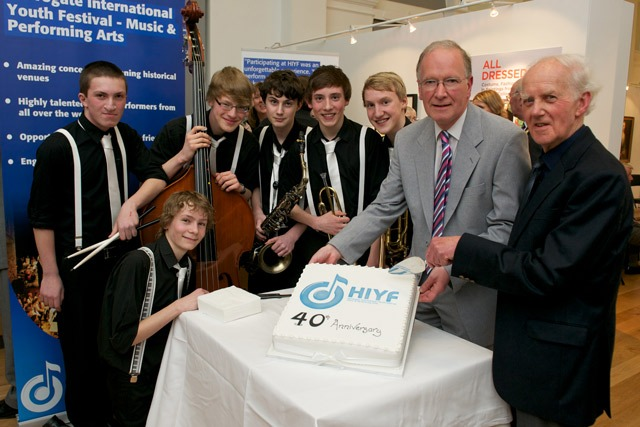Brace Yourselves, just some of the festival's young musical talent, join Chair of the Committee John Wood and Neil Richmond, one of the event's founders in celebrating 40 years with a specially commissioned cake from Bettys