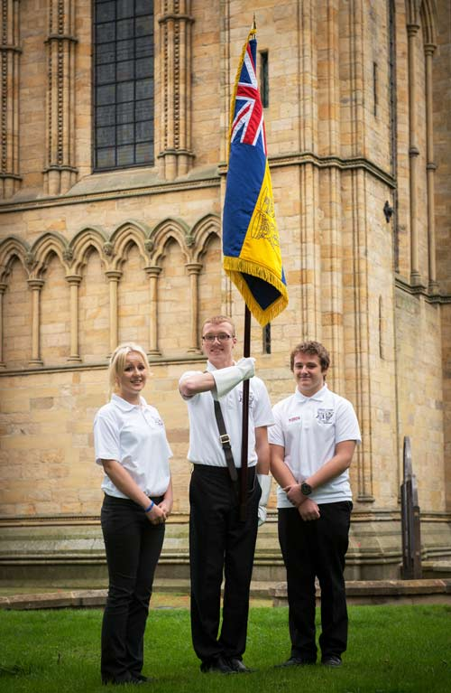 (left to right) Frankie Fitzwater, St Francis Xavier, Richmond; Jordan Radford, Outwood Academy, Ripon and Lewis Maclean, Bedale High School hold the North Yorkshire HMS Heroes standard outside Ripon Cathdral