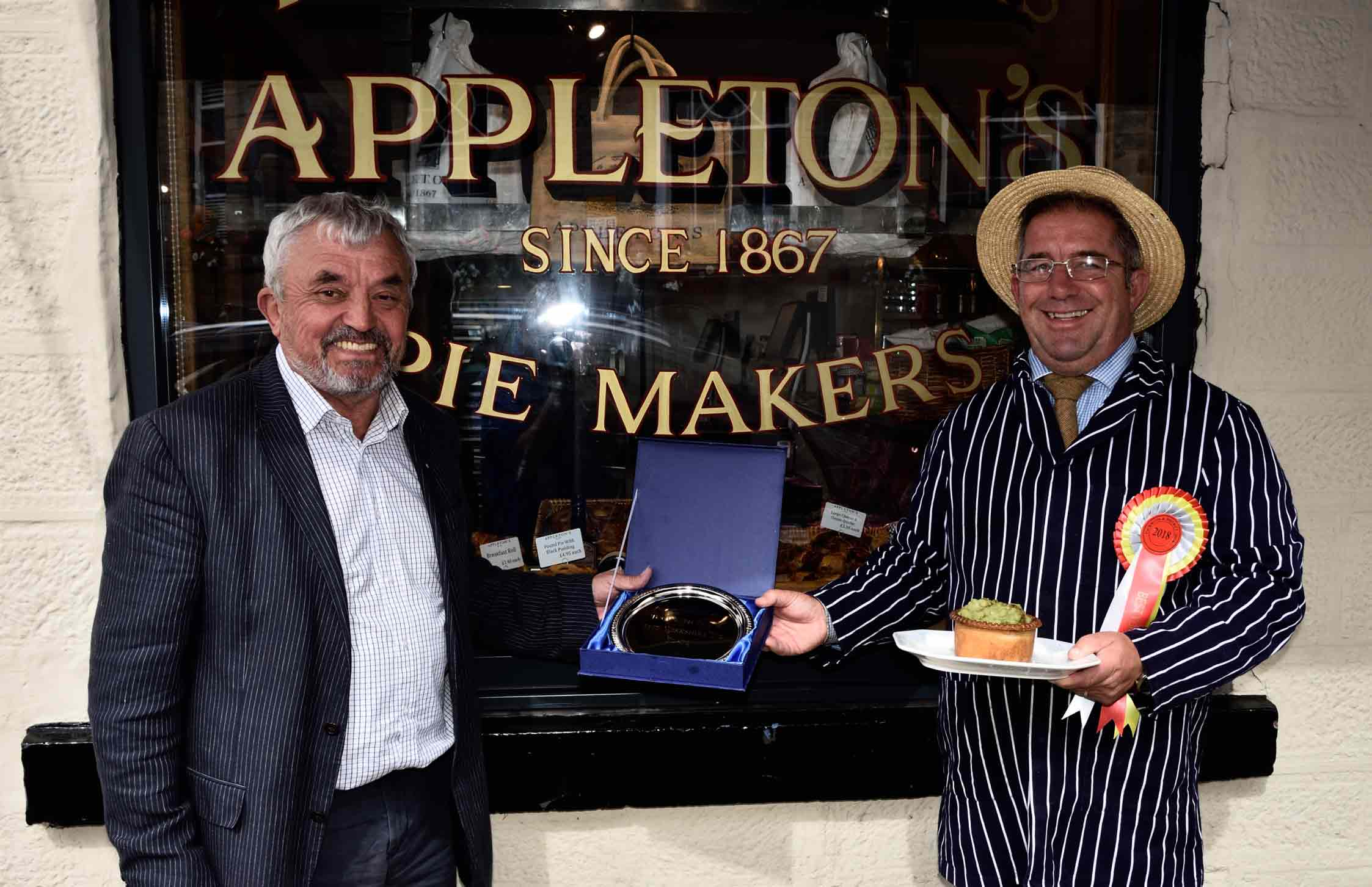 Award-winning pie maker Kevin Wilson of Appleton's Butchers receives his trophy and rosette from Tockwith Show vice-chairman Allan Robinison
