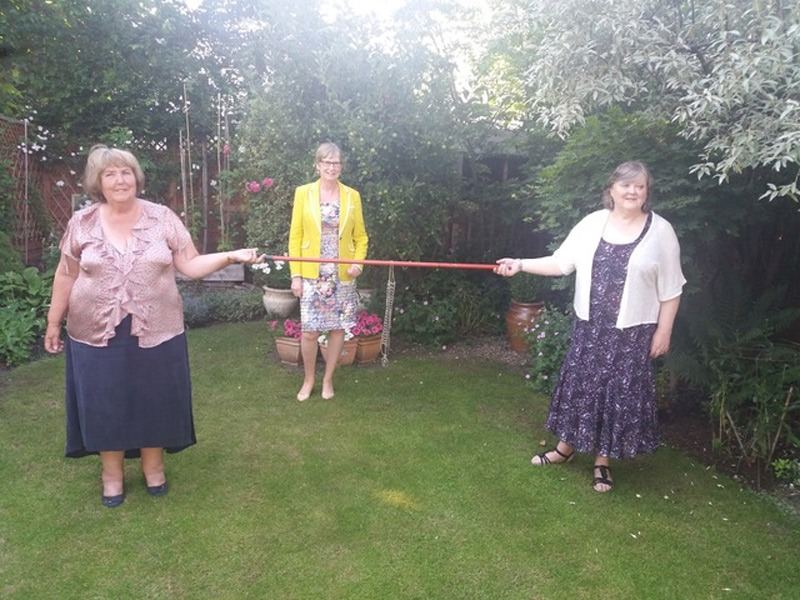 Past Presidents Sylvia Purser and Sue Williams with chain on broom handle