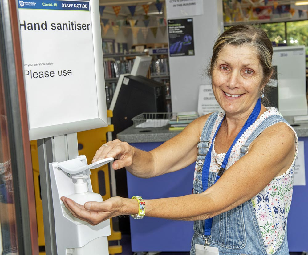 Library volunteer Carolyn McMahon demonstrates the hand sanitiser that will be in libraries